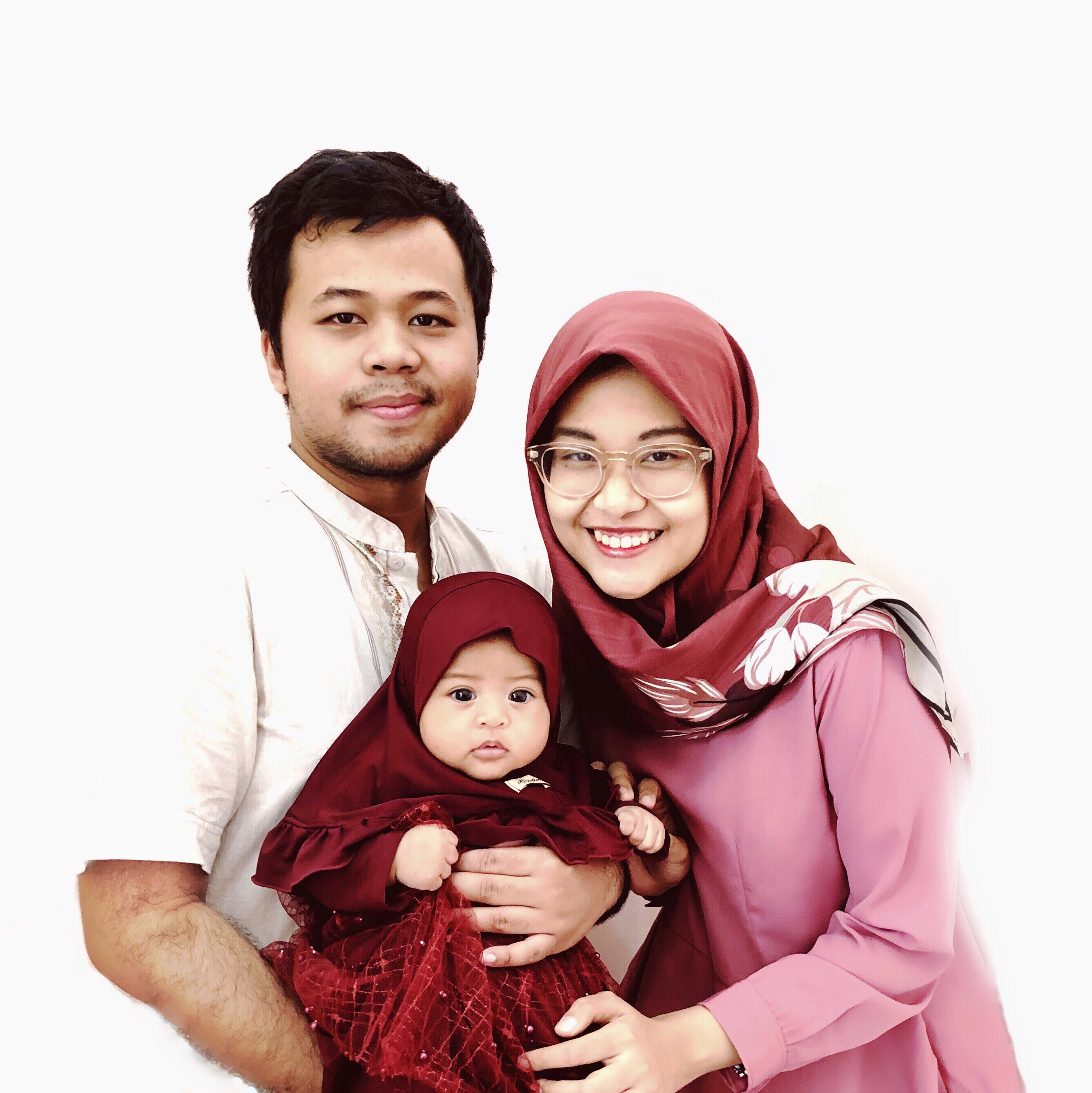 A couple pose with their baby daughter
