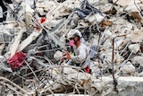 A rescuer wearing safety and breathing equipment moves through the waist-high rubble of a collapsed apartment building.