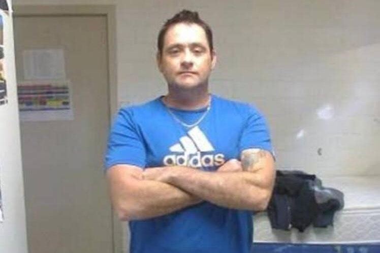 Man in a blue tshirt with arms crossed