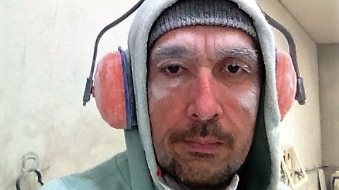 Tahir Ozkul covered with dust after cutting stone