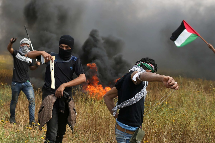A man holds an axe as his companion prepares stones to throw at israeli troops