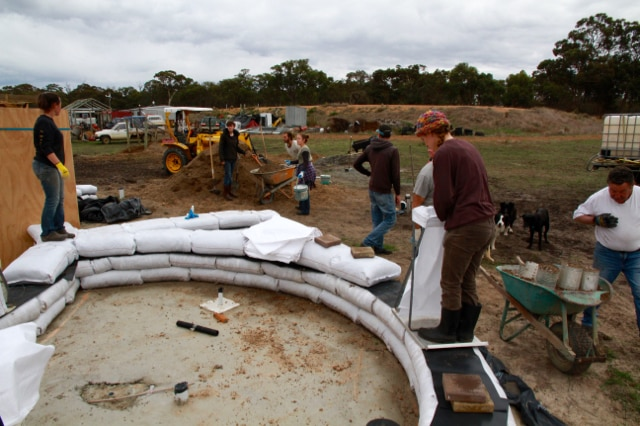 Volunteers lay down the first earth bags