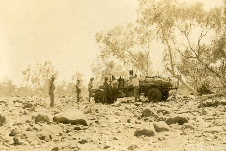 A few men stand around a mail truck it is parked on the rocky, uneven ground of a dried riverbed. The old photo is sepia-toned.