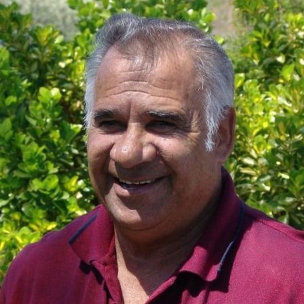 Aboriginal man in red shirt looks at camera