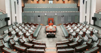 The House of Representatives, an expansive room with green carpet and chairs. There is nobody inside.