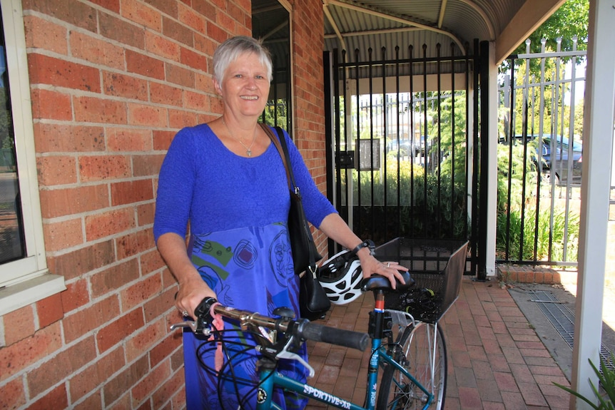 A woman in a  casual dress standing holding a bike