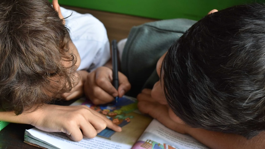 Two children drawing on a book