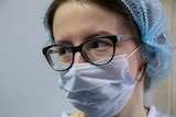 A medical worker wears a hair covering and a face mask