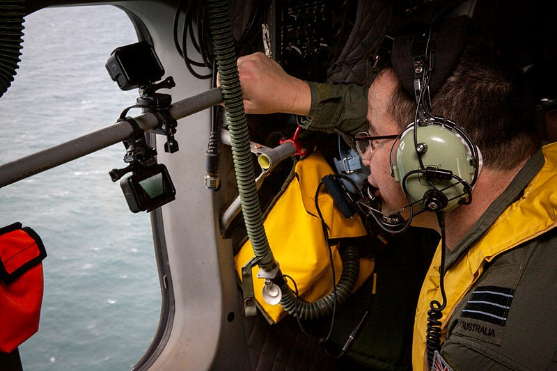A man in a rescue aircraft looks through a go pro while flying over the ocean