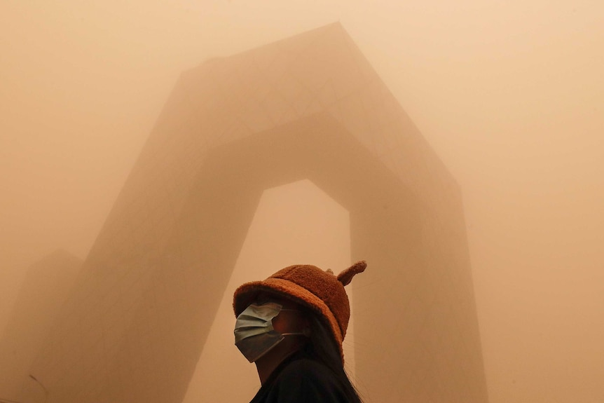 A woman stands in front of a modern building covered in smog in Beijing