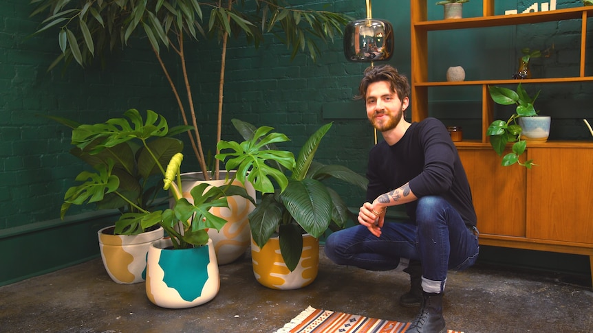 Plant stylist Ryan Klewer crouches beside various pots of plants, and shares tips on how to decorate home with indoor plants.