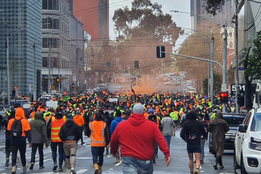 A crowd of hundreds, many in hi-vis jackets, march through Melbourne's CBD with an orange flare haze in the air.