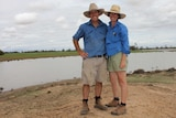 A couple in farm work clothes stand on a hill smiling with a big lake of water and green grass behind them