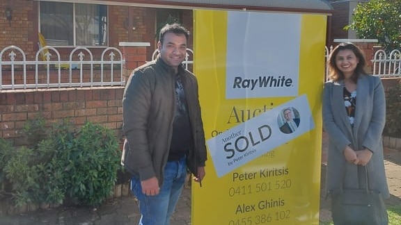 a man and a woman smiling infront of a SOLD sign on a house