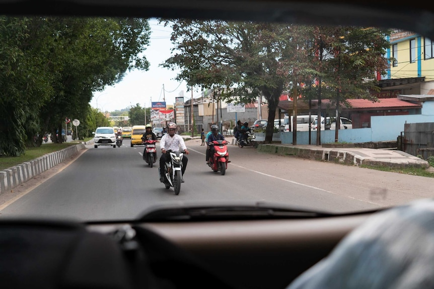 Through a car's rear window, men on scooters are seen driving on a street.