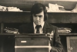 An aged photo of a young man sitting at a typewriter with newspapers piled behind him.