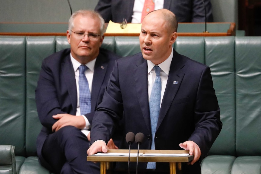 Josh Frydenberg stands at a podium and is photographed mid-speech, while Prime Minister Scott Morrison stands behind him.