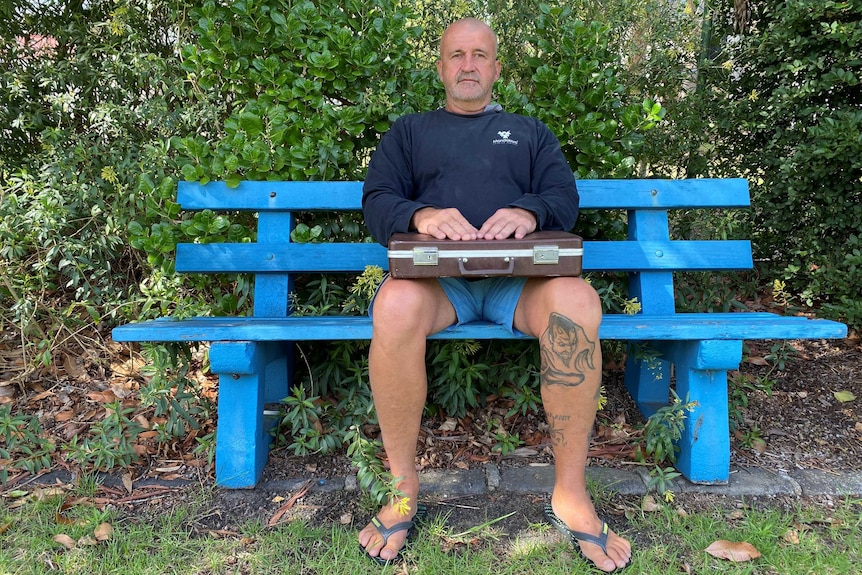 Rod Owen sits on a blue park bench with a brown briefcase on his lap.