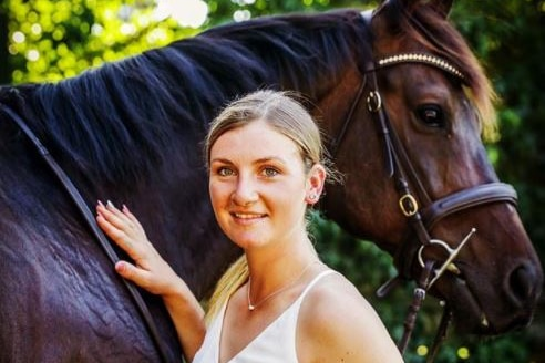 A woman in a white top pats a horse.