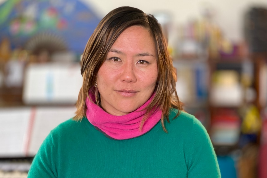 Delia Poon, wearing a green jumper, looking into the camera.
