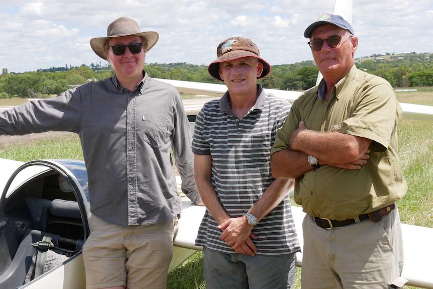Three men standing in front of glider