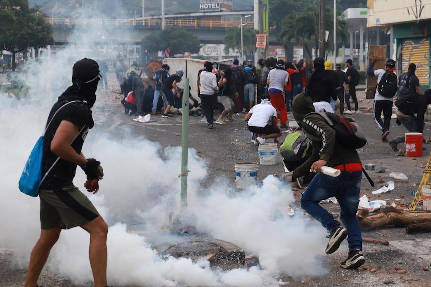 Men run through tear gas.