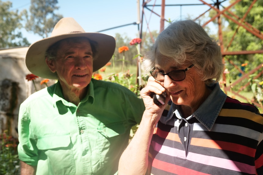 Man and woman standing in a flower garden. The woman holds a mobile phone to her ear.