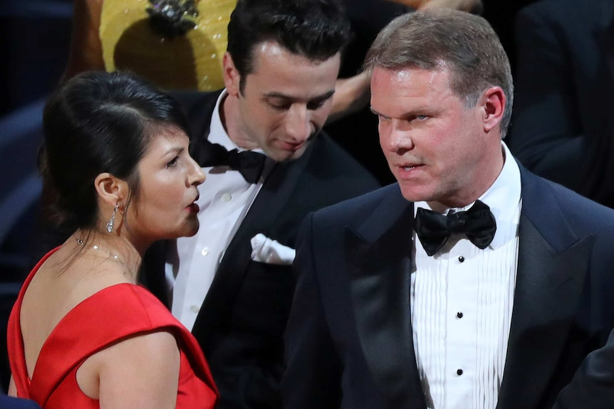 Brian Cullinan and Martha Ruiz confer on stage after the Best Picture was mistakenly awarded to La La Land instead of Moonlight
