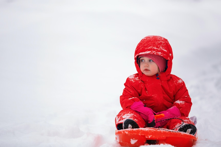 A young child on a red toboggan in the snow.