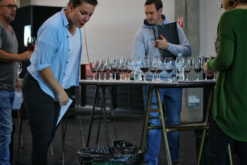 A judge at the Royal Melbourne Wine Awards spits into a bucket.