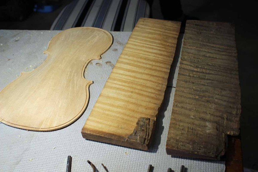 The front of a violin next to two blocks of wood.