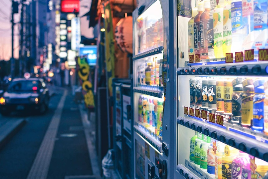A Japanese street scene at evening with two neon-lit, brightly coloured vending machines, selling drinks, in the foreground.