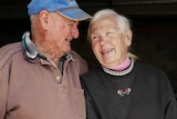 An older man and woman laugh and look fondly at each other