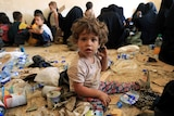 A toddler covered in dirt sits amongst piles of rubbish.