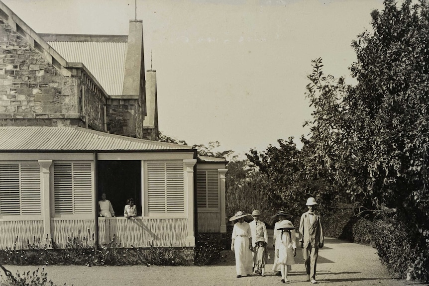 Black and white photo of a group of people walking away from an old brick house in early 1900s outfits.