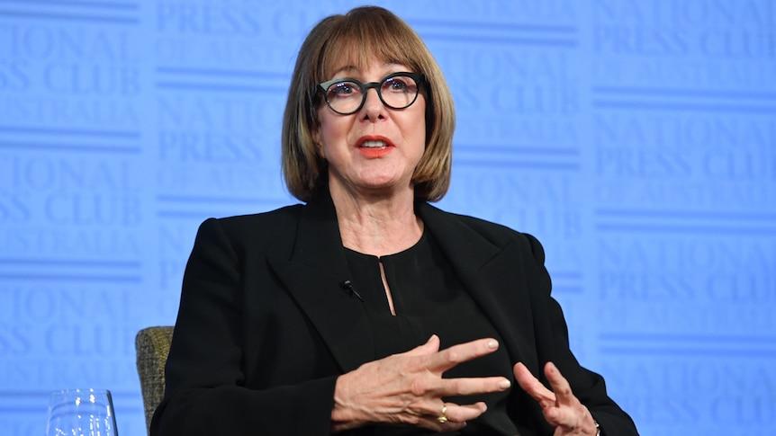 a woman wearing glasses talking