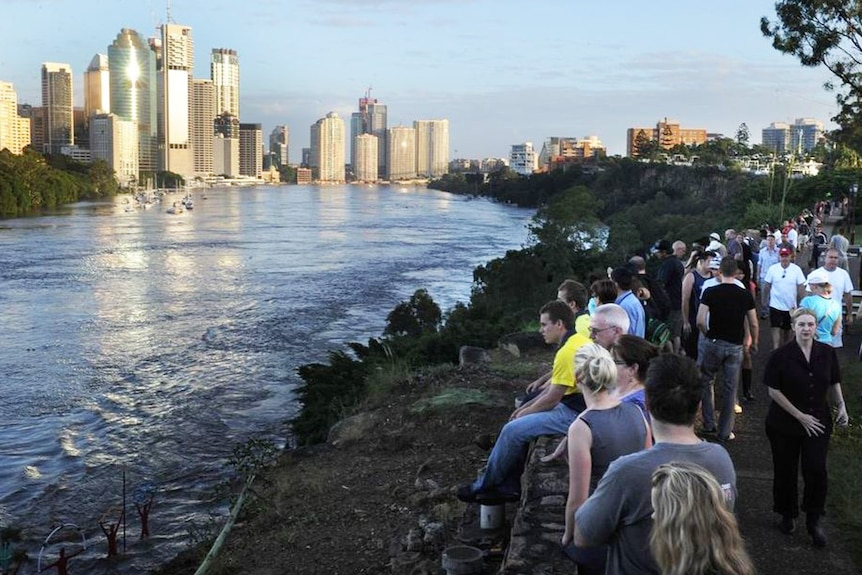 Residents watch the Brisbane River flood peak in the CBD at sunrise at the Kangaroo Point cliffs on January 13, 2011.