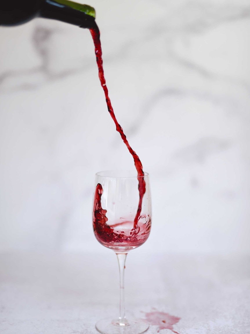Wine is poured from up high into a glass, splashing at the edges.