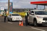 A police officer talks to a driver through the window of a car travelling into Mount Gambier from Victoria.
