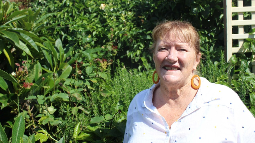 An older woman standing in a garden, smiling.
