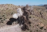 On a clear day, you view an aerial photo of an explosion on a mountainside with dirt and rocks flying into the air.