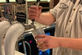 A man pours a beer into a glass from a beer tap