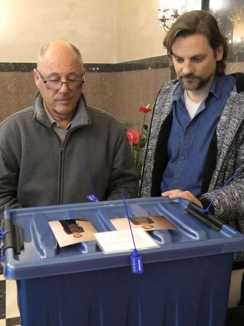 Two men look at a blue box.