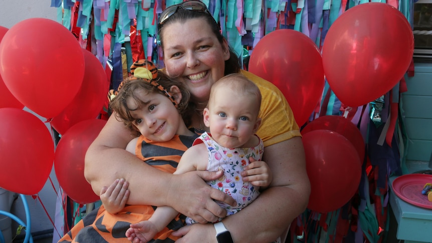 A mother hugs her two daughters with red balloons on either side.