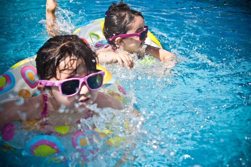 Two young kids wearing sunglasses floating in a swimming pool on pool toys