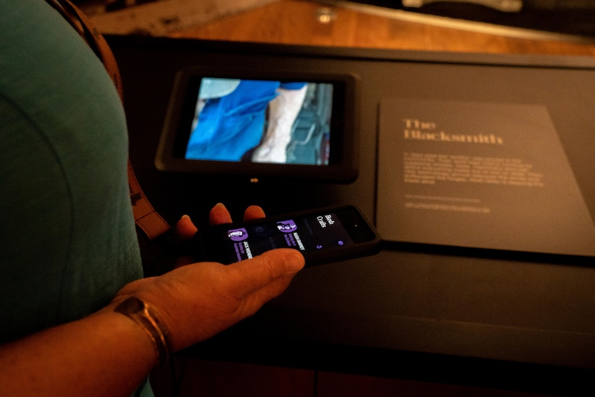 A close-up shot of a hand holding an iPod Touch in front of a small iPad screen in a museum.