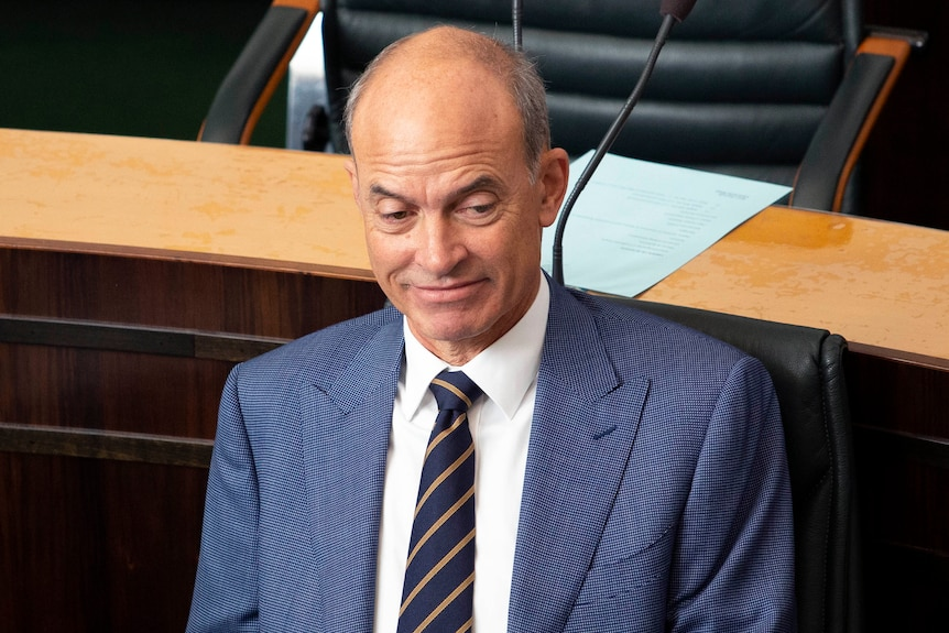A man in a blue suit sits in Parliament