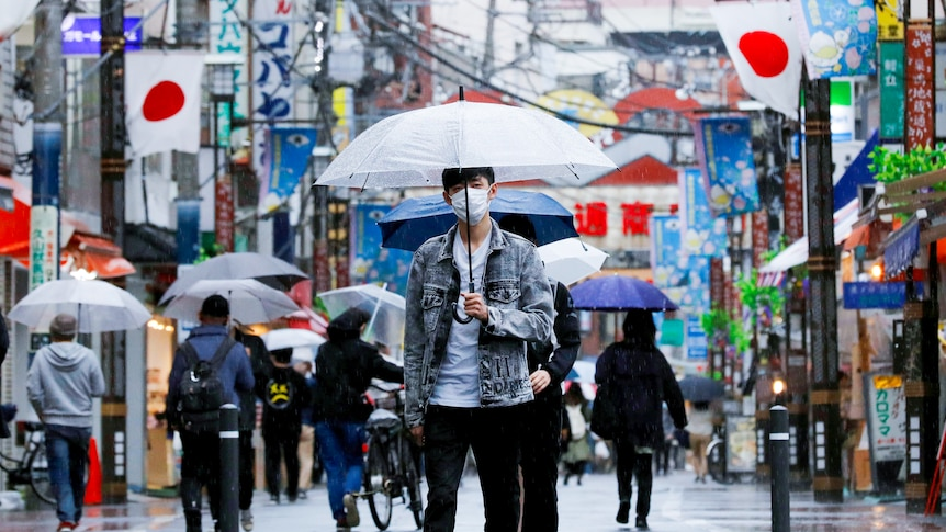 A Japanese man in a face mask holds an umbrella while walking down a Tokyo street