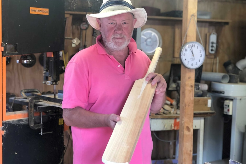 A man standing in a shed holds up a hand-carved cricket bat.