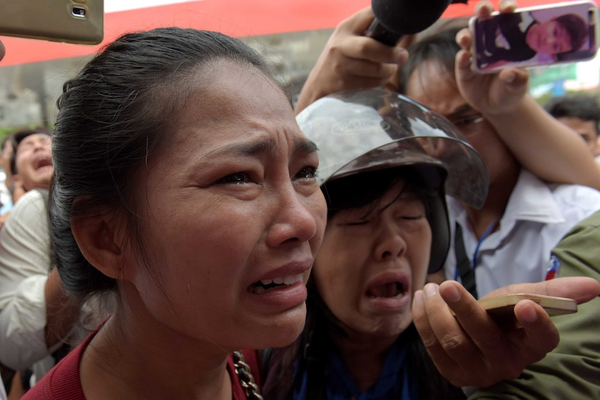 Cambodians gather outside a store where political analyst Kem Ley was shot dead in Phnom Penh.